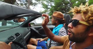 Black handsome men driving hands free with his friends in convertible