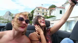 Blonde and brunette girl riding through town in cabriolet