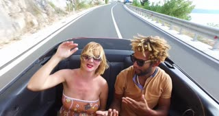 Blonde woman dancing with black friend in the back seat of convertible