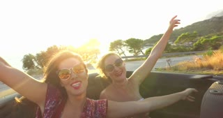 Boho dressed women enjoying sunset riding at the back seat of convertible
