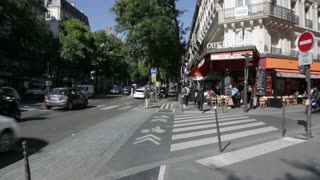 Busy street cafe with cyclist passing on cycle lane in Paris
