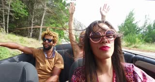Cheerful multi ethnic students enjoying vacation driving in red convertible