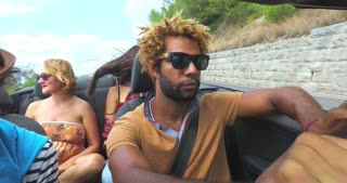 Close up of handsome black man driving three people in convertible car