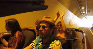 Four friends driving through tunnel in convertible car