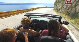 Friends dancing and waving arms driving on road along coast in red convertible