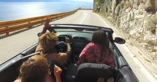Friends having fun driving on the road along the coast in red convertible
