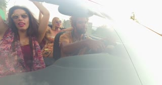 Front view of young multi-ethnic friends driving in red convertible