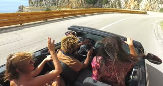 Group of friends driving on the road along the coast in red convertible