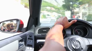 Handsome black man holding his left hand on the steering wheel of a convertible