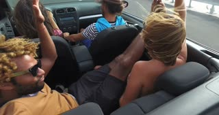 Handsome black man sticking his feet up of the convertible riding with friends