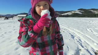 Little girl eating a snow ball in the mountains