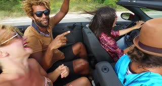 Multi ethnic couple having fun riding in back seat of convertible with friends
