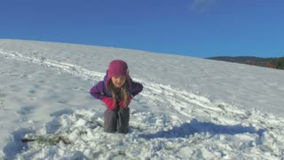 Slow motion of little girl jumping in the snow