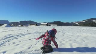 Small girl playing in snow in mountains
