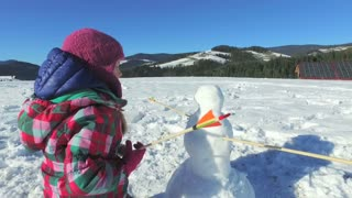 Small girl playing snowman in mountains