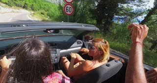 Two attractive girls driving in convertible with the top down