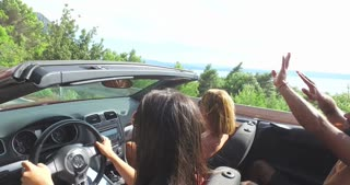 Two attractive girls waving their arms driving in convertible car with friends
