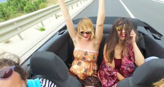 Two beautiful young women raising their arms up while riding in convertible