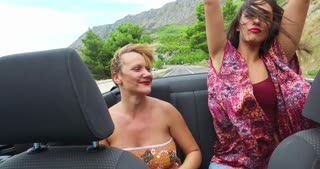 Two happy women partying in cabriolet