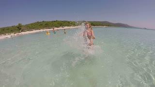 Woman in sea splashing water playfully