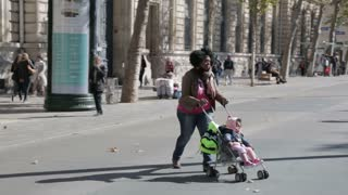 Woman of African origin, pushing child in stroller on Place de la Republique