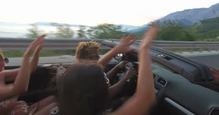 Young friends enjoying their road trip in convertible car