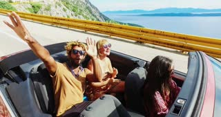 Young happy people on holiday having fun driving in red convertible, graded