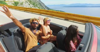 Young happy people on summer holiday having fun driving in red convertible