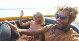 Young mixed race couple having fun in back seat of convertible
