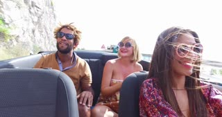Young multi-ethnic students enjoying summer vacation driving in red convertible