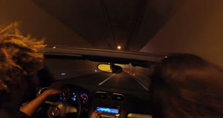 Young people driving through tunnel in convertible car