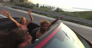 Young people enjoying summer holiday driving in convertible
