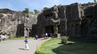 View at the entrance to Aurangabad caves, with people passing.
