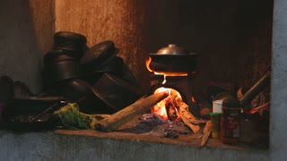 View burning fire heating a pot for cooking in local kitchen in Sri Lanka