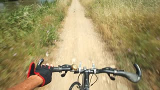 View from handlebars of man on bike on dirt track pov
