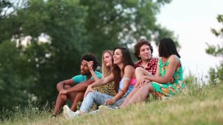 View of a group of five friends sitting on the grass and having a lot of fun taking selfies.