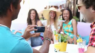 View of a man's hand holding a mobile phone and taking pictures of three beautiful, young women on terrace cafe on a summer day.