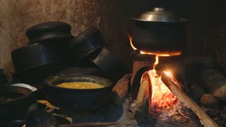 View of burning fire heating a pot for cooking in local kitchen in Sri Lanka