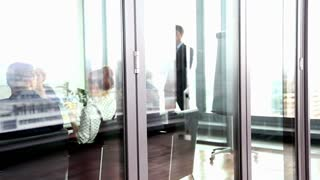 View of business people on a meeting in conference room behind glass wall, graded