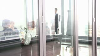 View of business people on a meeting in conference room behind glass wall