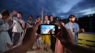 View of hands holding phone and filming happy group of friends dancing