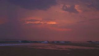 View of Hikkaduwa beach at sunset while waves are splashing
