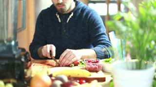 View of man hands cutting strawberries on wooden board, graded