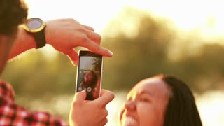 View of man's hand holding a mobile phone and taking pictures of woman at sunset, graded warmer.