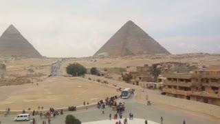 View of tourists walking around Giza pyramids