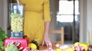 View of woman hands pouring water in blender with pineapple and avocado, in slow motion