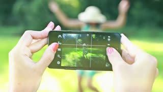 View of woman's hand holding a mobile phone and taking pictures of her friend dancing and posing in the park.
