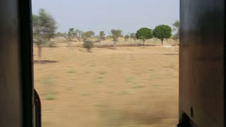 View on rural landscape in Jodhpur from train door during ride.