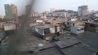 View on slum in Mumbai during a train ride.