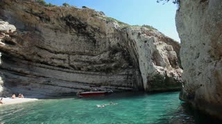 VIS, CROATIA - SEPTEMBER 9: Men standing on cliff ready to dive in Stiniva bay on September 9, 2013 in Vis, Croatia. The stunning landmark bay of Stiniva attracts tourists from all around the world.